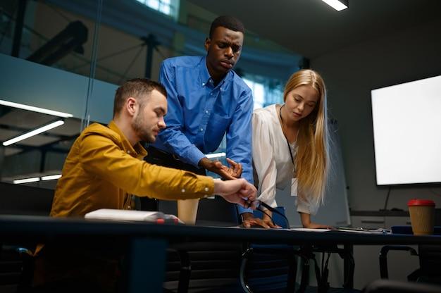 Équipe de jeunes managers, discussion dans le bureau d'affaires informatique. travail d'équipe et planification professionnels, brainstorming de groupe et travail d'entreprise