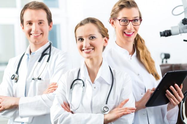 Équipe de jeunes médecins en clinique avec tablette