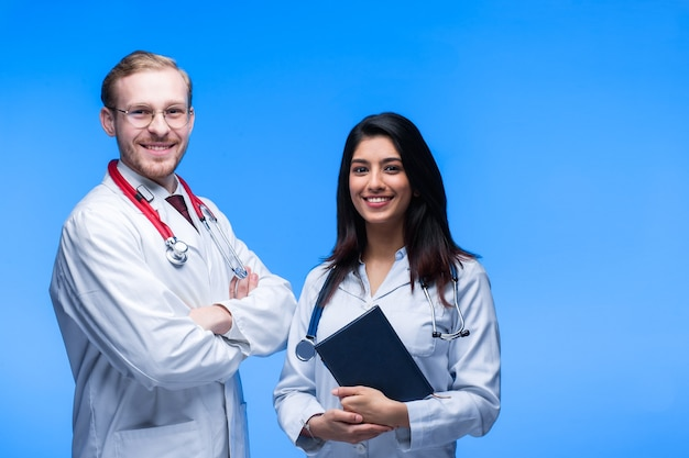 Une équipe de jeunes médecins. personnes multinationales - médecin, infirmière et chirurgien sur fond bleu. un groupe d'étudiants en médecine de différentes nationalités regarde dans la cellule.