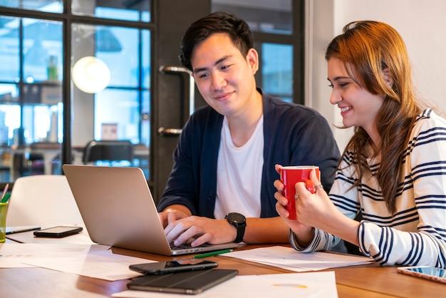 Équipe de jeunes startups asiatiques en uniforme décontracté discutant et travaillant ensemble dans un espace de travail moderne.