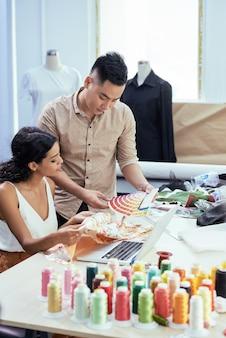 Équipe de jeunes tailleurs utilisant une palette d'échantillons de couleurs pour choisir la nuance parfaite de fil pour la soie ...