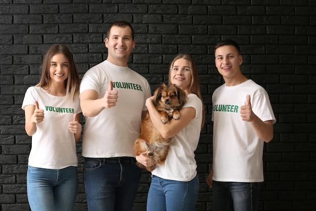 Équipe de jeunes volontaires avec chien sur une surface sombre