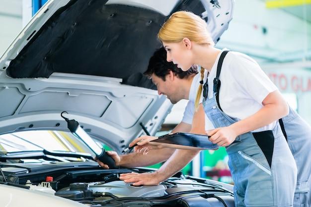 Équipe de mécanicien travaillant dans un atelier automobile