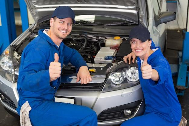 Équipe de mécaniciens souriant à la caméra
