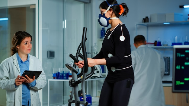 Équipe de médecins chercheurs surveillant l'endurance des femmes sportives de performance portant un masque de course cross trainer. docteur en sciences de laboratoire mesurant la vo2 d'une sportive, tenant une tablette expliquant l'état de santé