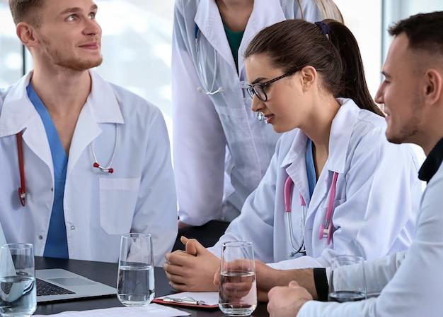 Équipe de médecins discutant du diagnostic à table en clinique