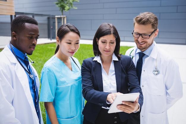 Équipe de médecins discutant sur tablette numérique