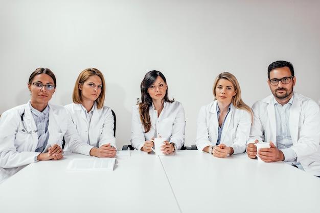 Une équipe de médecins regarde la caméra alors qu'elle est assise dans la salle de conférence. espace de copie.
