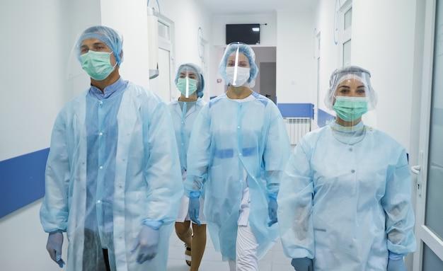 Une équipe de médecins en tenue de protection des travailleurs médicaux masqués marchent dans le couloir d'un hôpital moderne...