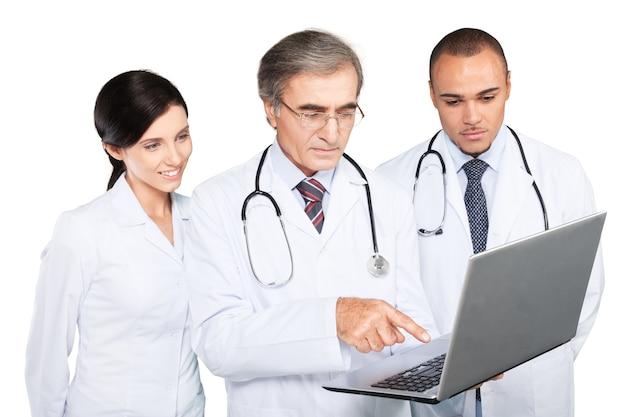 Équipe médicale confiante utilisant un ordinateur portable isolé sur blanc