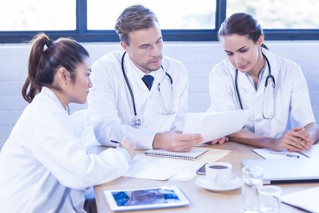 Équipe médicale discutant en réunion dans une salle de conférence