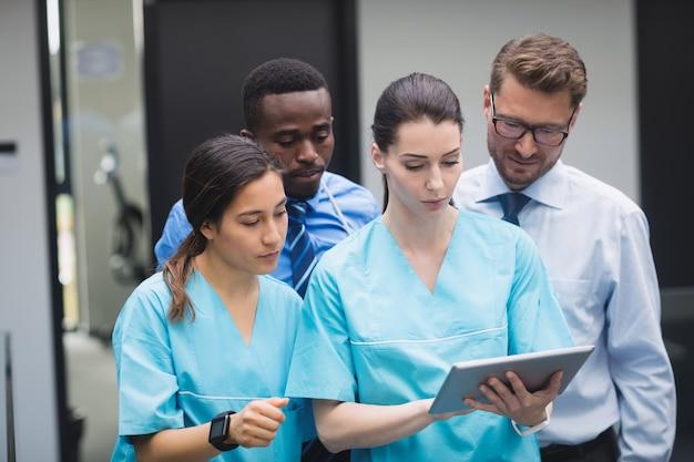 Équipe médicale discutant sur tablette numérique