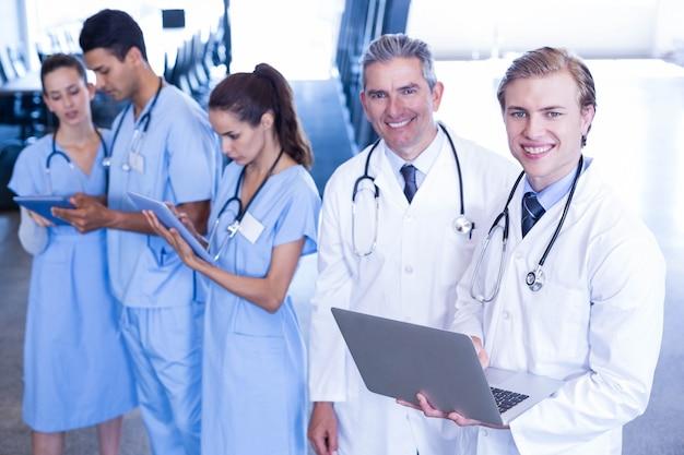 Équipe médicale discutant et utilisant un ordinateur portable et une tablette numérique à l'hôpital