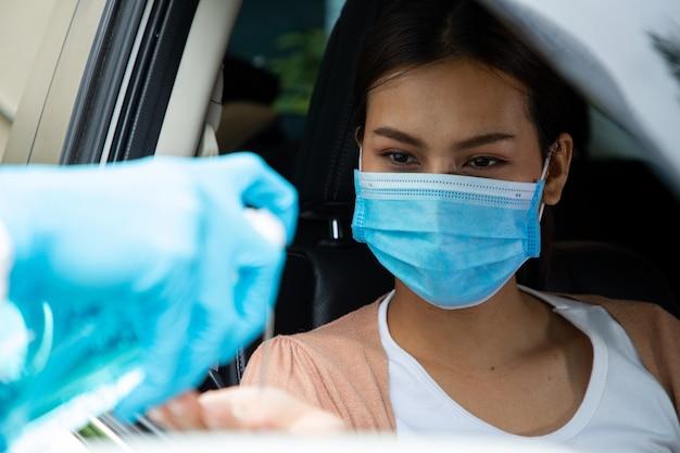 Équipe médicale du personnel de l'epe donnant du gel d'alcool pour l'hygiène des mains coronavirus à l'intérieur de la voiture