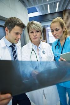 Équipe médicale examinant le rapport de radiographie dans le couloir