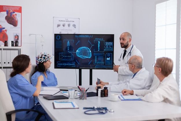 Équipe médicale hospitalière faisant des recherches sur l'activité cérébrale à l'aide d'un casque avec capteurs