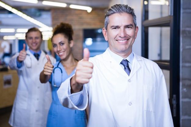 Équipe médicale levant les pouces et souriant