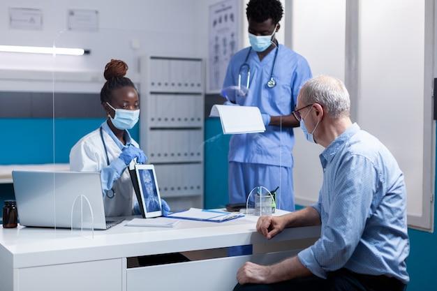 Équipe médicale de noirs parlant à un patient âgé
