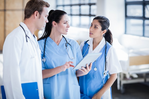 Équipe médicale à la recherche de tablet pc dans le couloir