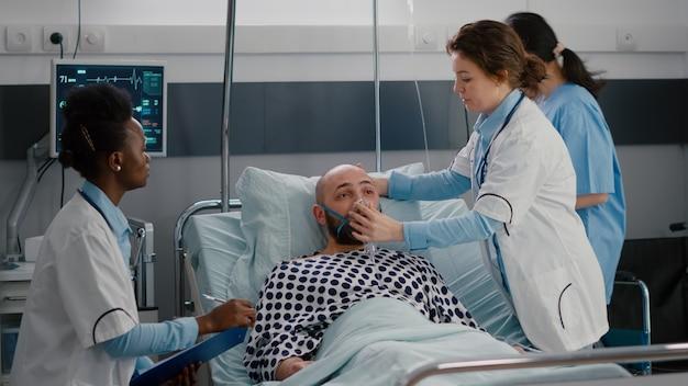 Équipe médicale surveillant le pouls d'un homme malade pendant une urgence respiratoire