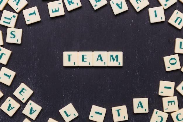 Équipe de mots en lettres de scrabble sur fond noir