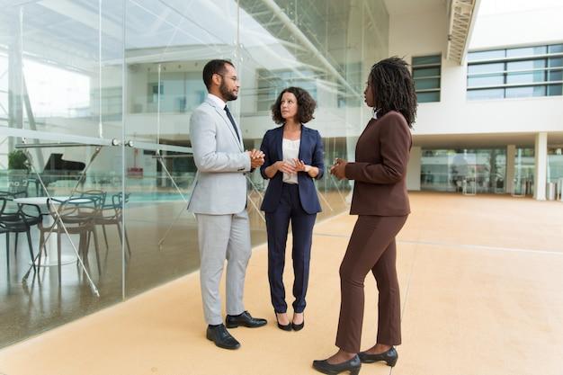 Équipe multiethnique discutant d'un projet près d'un immeuble de bureaux