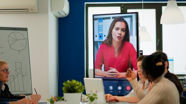 Équipe multiethnique écoutant une femme d'affaires confiante webinaire conférencier coach entrepreneur enseignant parlant regardant la caméra webcam enregistrer une formation vidéo vlog faisant une conférence téléphonique d'affaires en ligne