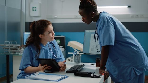 Équipe multiethnique d'infirmières regardant une tablette et parlant des soins de santé