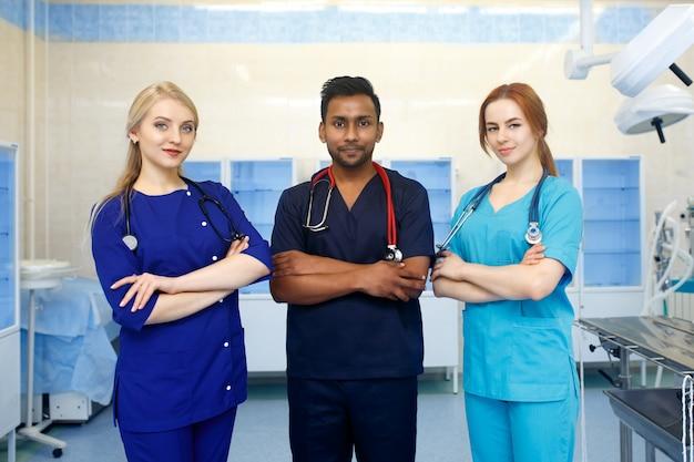 Équipe multiraciale de jeunes médecins dans un hôpital debout dans une salle d'opération
