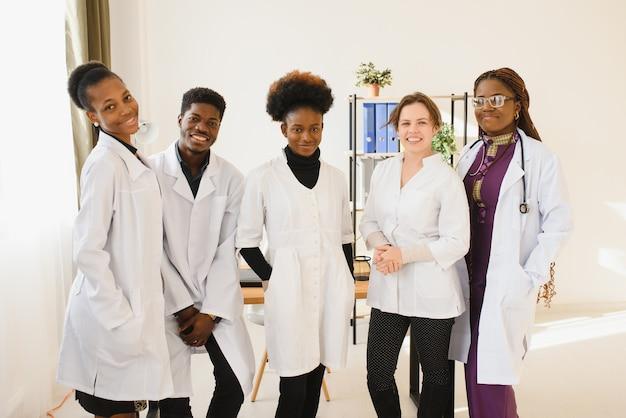 Équipe multiraciale de médecins dans un hôpital debout dans un couloir prêt à faire un tour de salle