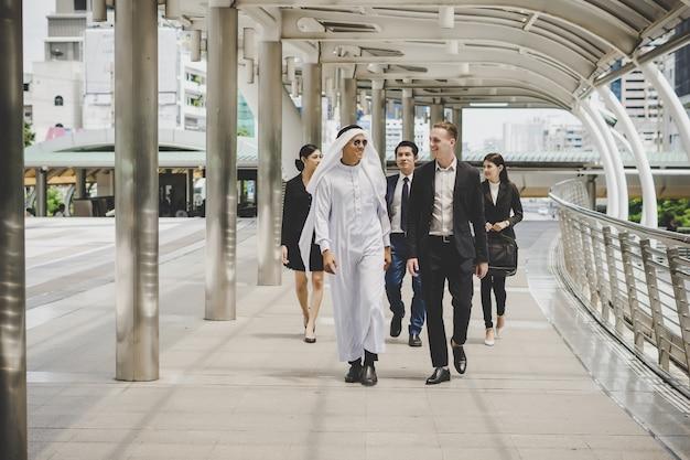 Équipe de partenaires commerciaux se promenant et discutant du travail.
