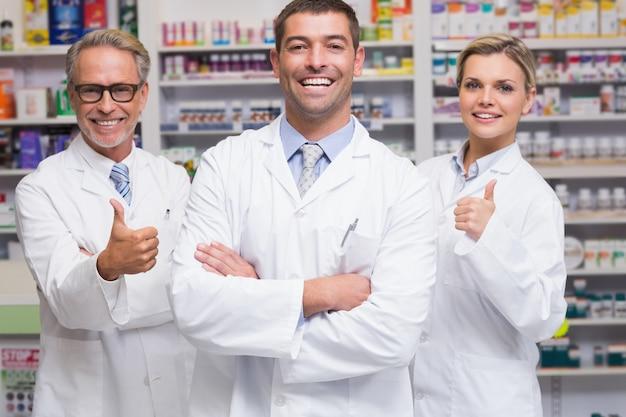 Équipe de pharmaciens souriant à la caméra à la pharmacie