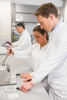 Équipe de pharmaciens utilisant la presse pour fabriquer des pilules