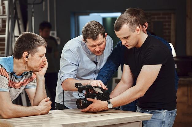 Équipe professionnelle de cameramen avec un réalisateur filmant des publicités