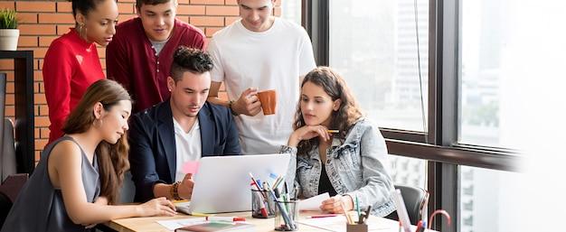 Une équipe de professionnels occasionnels multiethnique, un brainstorming devant un ordinateur portable