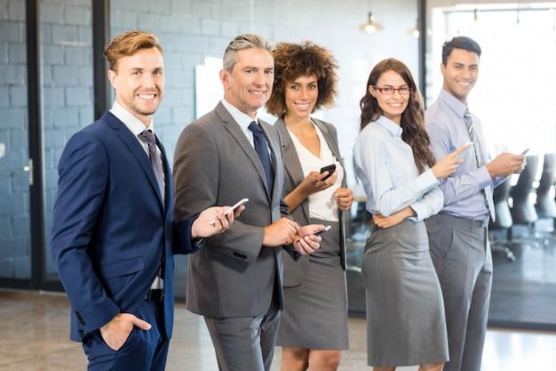 Équipe de professionnels utilisant leur téléphone portable au bureau