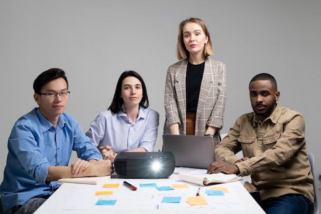 Équipe de quatre courtiers interculturels à succès assis à table avec projecteur et documents financiers et préparant la présentation au bureau