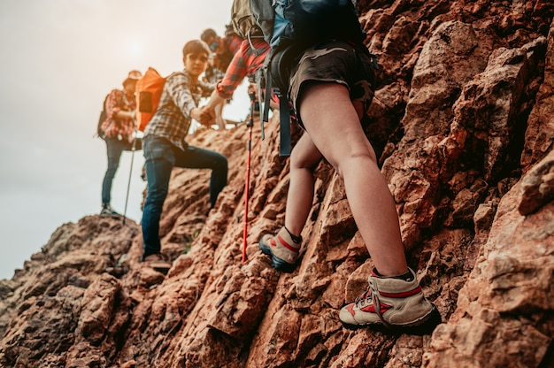 L'équipe de randonneurs de groupe aide son amie à gravir la dernière section du coucher de soleil dans les montagnes
