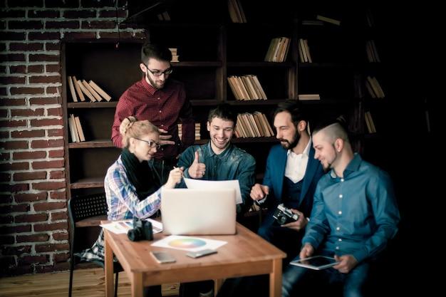 Équipe de rédacteurs discutant d'un nouveau projet publicitaire dans un bureau moderne