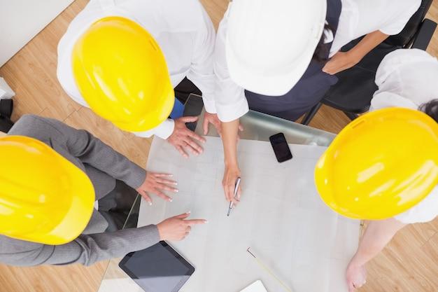 Équipe regardant un plan de construction avec des casques