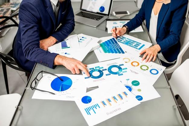 L'équipe de responsable marketing ou analyc travaille sur des cartes papier à la table. image centrée sur les documents sans visage