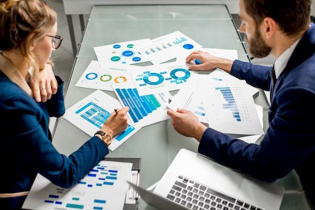 L'équipe de responsable marketing ou analyc travaille sur des cartes papier à la table. image centrée sur les documents