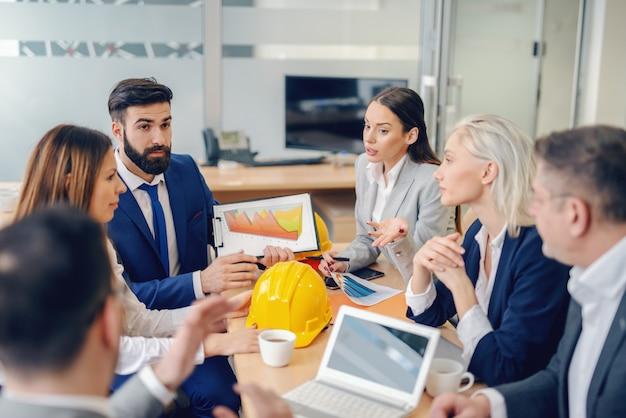 Équipe réussie d'architectes se réunissant en salle de conférence. le travail d'équipe divise la tâche et multiplie les succès.