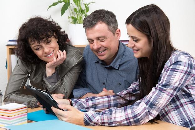 Équipe réussie de gens d'affaires regardant ordinateur tablette pour une présentation.