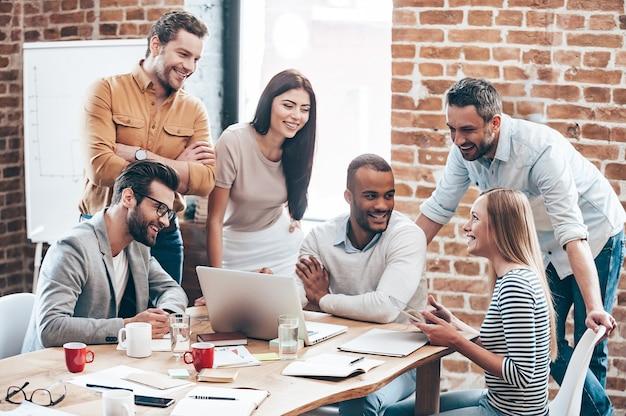 Équipe réussie. groupe de jeunes joyeux discutant de quelque chose avec le sourire et faisant des gestes tout en se penchant vers la table au bureau