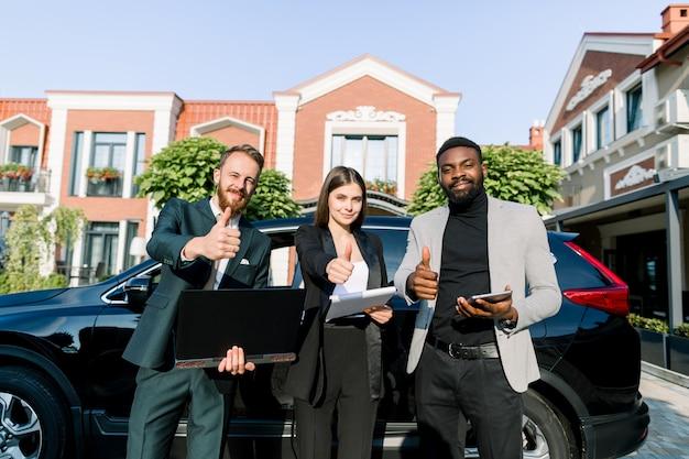 Équipe réussie multiethnique, deux hommes d'affaires et une femme d'affaires, tenant une tablette, un ordinateur portable et des papiers, montrant les pouces vers le haut, debout près de la voiture à l'extérieur. concept d'équipe, d'affaires, de technologie