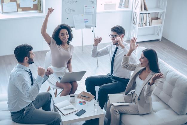 Équipe réussie. vue de dessus d'un groupe de quatre jeunes faisant des gestes et ayant l'air heureux assis sur le canapé au bureau