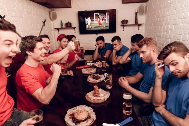 Équipe rouge et bleue sont assis au bar des sports.