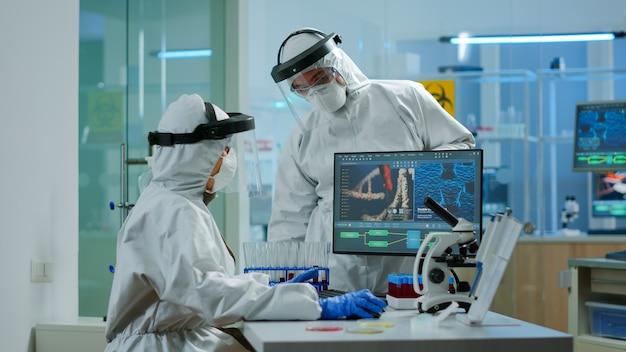 Équipe de scientifiques en costume de protection se disputant devant un ordinateur en regardant le développement du virus dans un laboratoire équipé. équipe de scientifiques analysant l'évolution des vaccins à l'aide de la haute technologie pour la recherche d'un traitement
