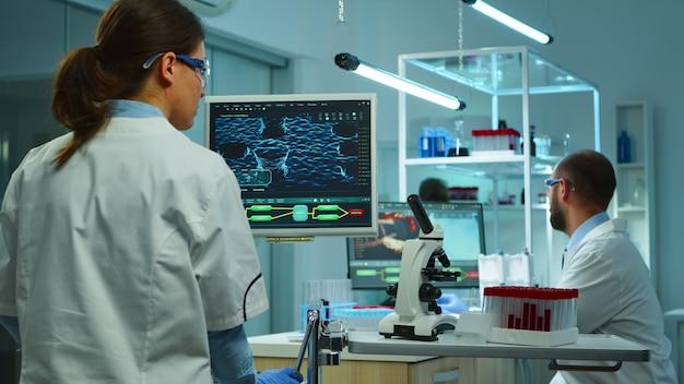 Équipe de scientifiques de la recherche médicale menant le développement de vaccins à l'aide de haute technologie, de tubes à essai, de micropipettes et par écrit les résultats d'analyse sur ordinateur dans un laboratoire moderne équipé la nuit